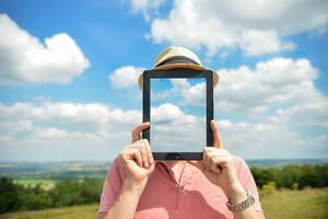 Concept Of Man Holding iPad In Front Of Face With Clouds And Countryside